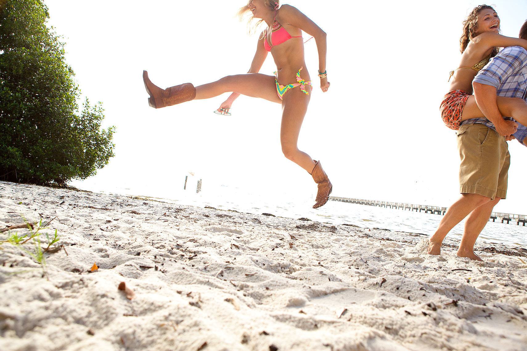 woman in bikini and boots jumps on beach_Robert-Holland.jpg