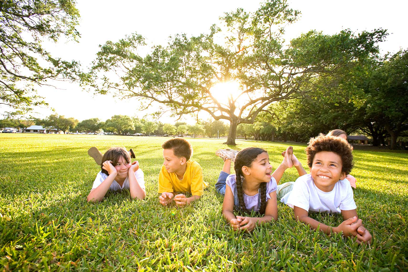 four children laying on grass hanging out at park, Florida_Robert_Holland.jpg