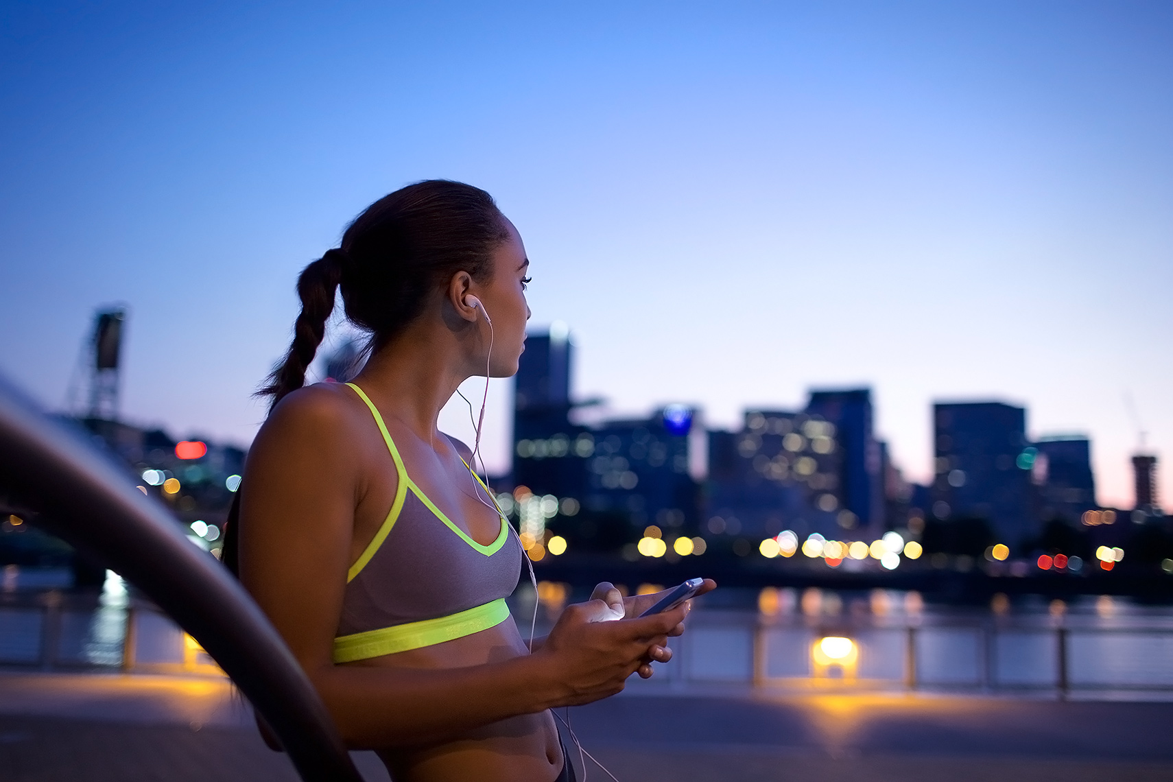 Robert-Holland_MG_9670_young woman with evening city skyline, texting after a run
