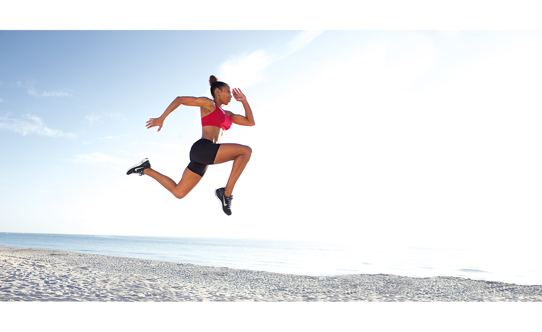 Robert_Holland_female_athlete_jumping-high-in-air-along-shore-MG_9709