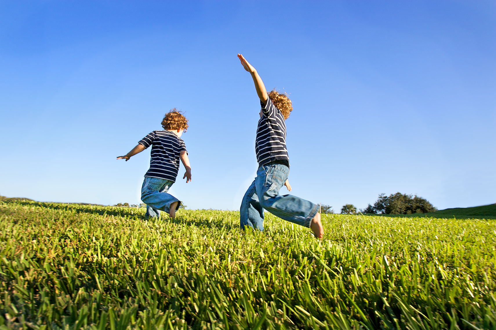 young boys running, playing airplane in field_Y0U4598_Robert-Holland.jpg