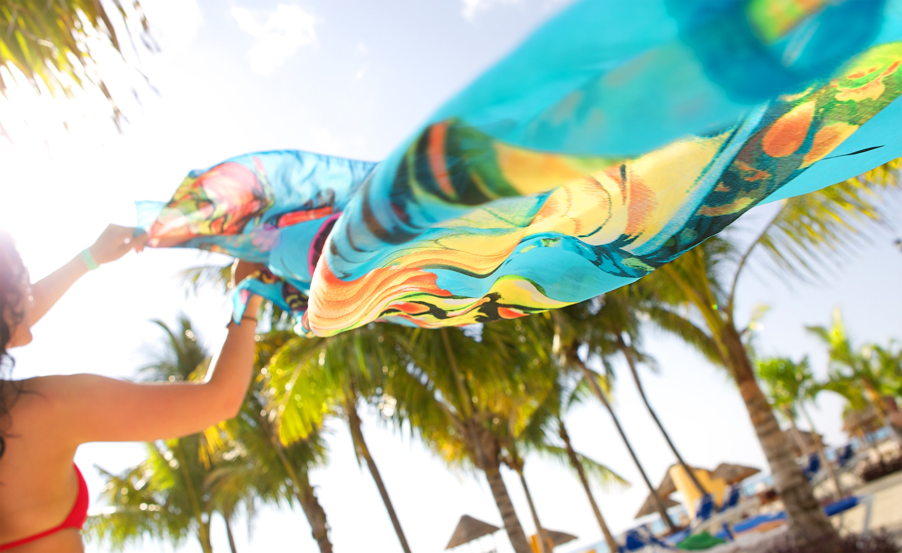 woman letting wind blow colorful fabric in the breeze, with palm trees at resort, Mexico_Holland_resort lifestyle photography