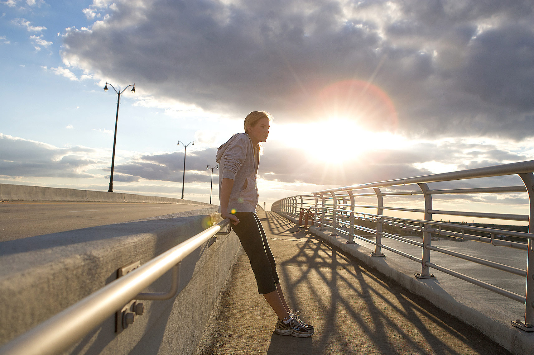 _Y0U8131_Robert_Holland__teenage runner leaning against bridge railing, resting with sunset and dramatic clouds